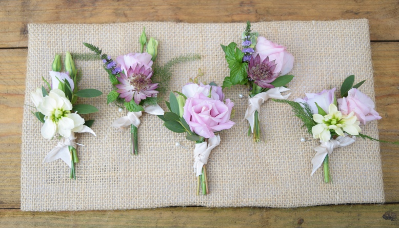 Wedding buttonholes laid onto a hessian back
