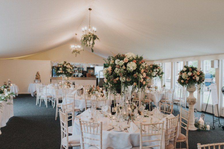 Wedding breakfast flowers set within a marquee