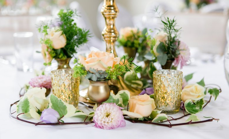 Dainty vases filled with flowers accented with candlelight and trailing foliages