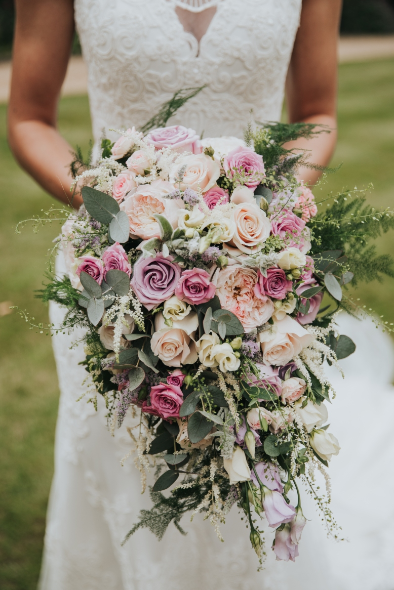 Oversized trailing handed bridal bouquet in pinks and lilacs.